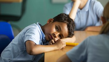 Tired boy at school desk