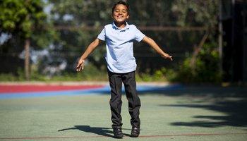 Boy doing a star jump in school uniform