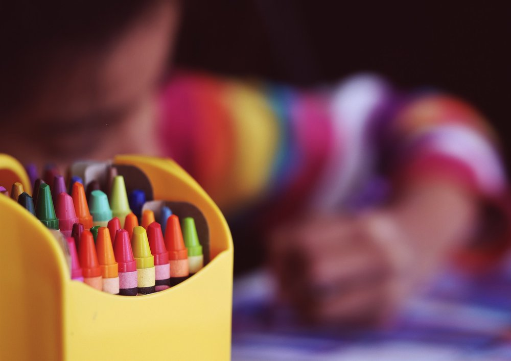 Close up of crayons with child in background