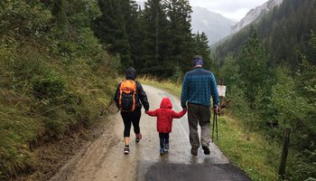 Family with young child hiking on a rainy path through the mountains