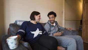 Foster carer with teenager chatting on a couch