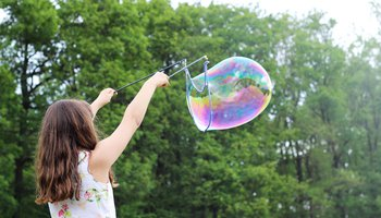Girl with long hair creating a large bubble in the air
