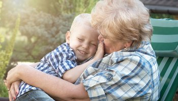 Granmother hugging grandson in garden