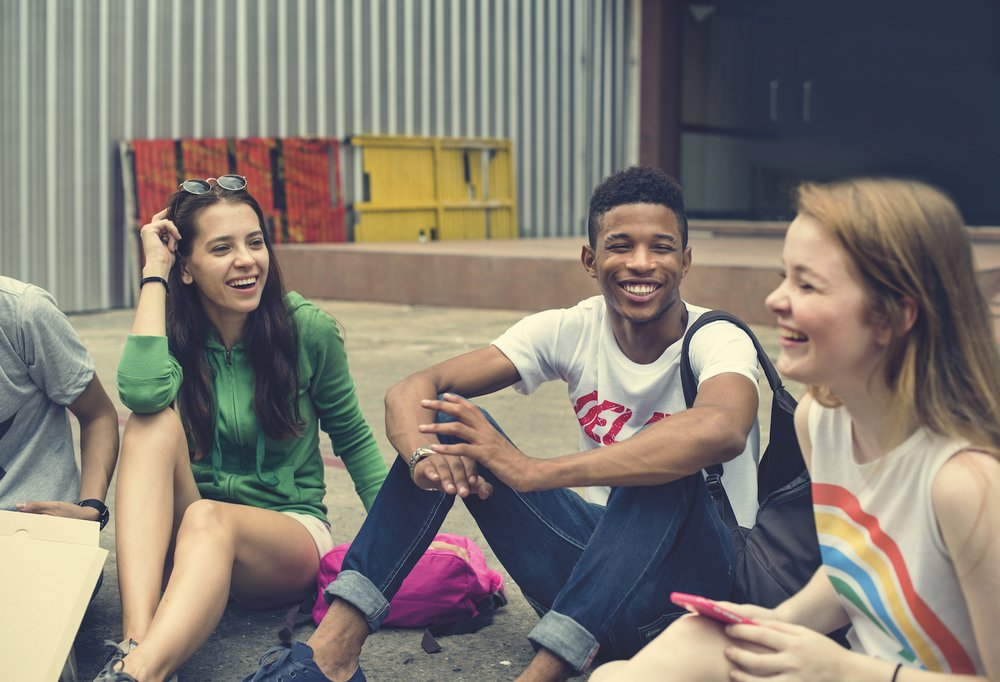 Group of happy teens sitting in a circle on the ground and laughing