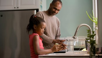 Happy father and daughter washing hands at kitchen sink