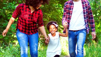 Happy father and mother holding daughters hands and walking through woods