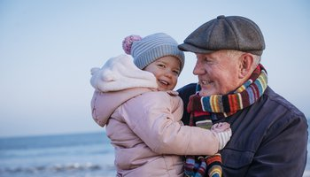 Happy grandfather and toddler hugging on the beach