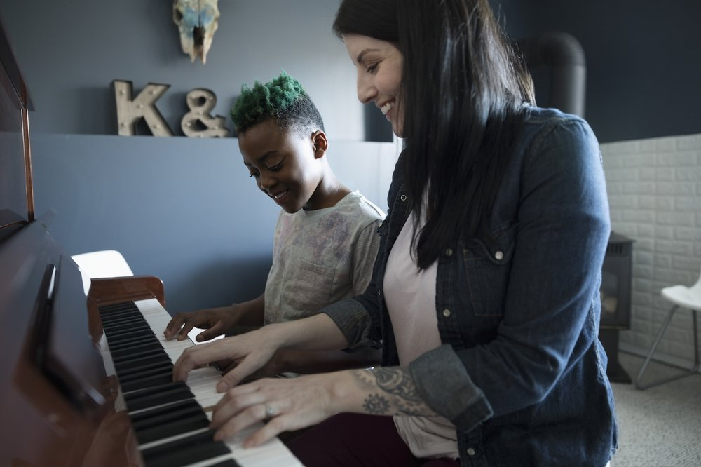 Happy woman and young girl sat playing piano together