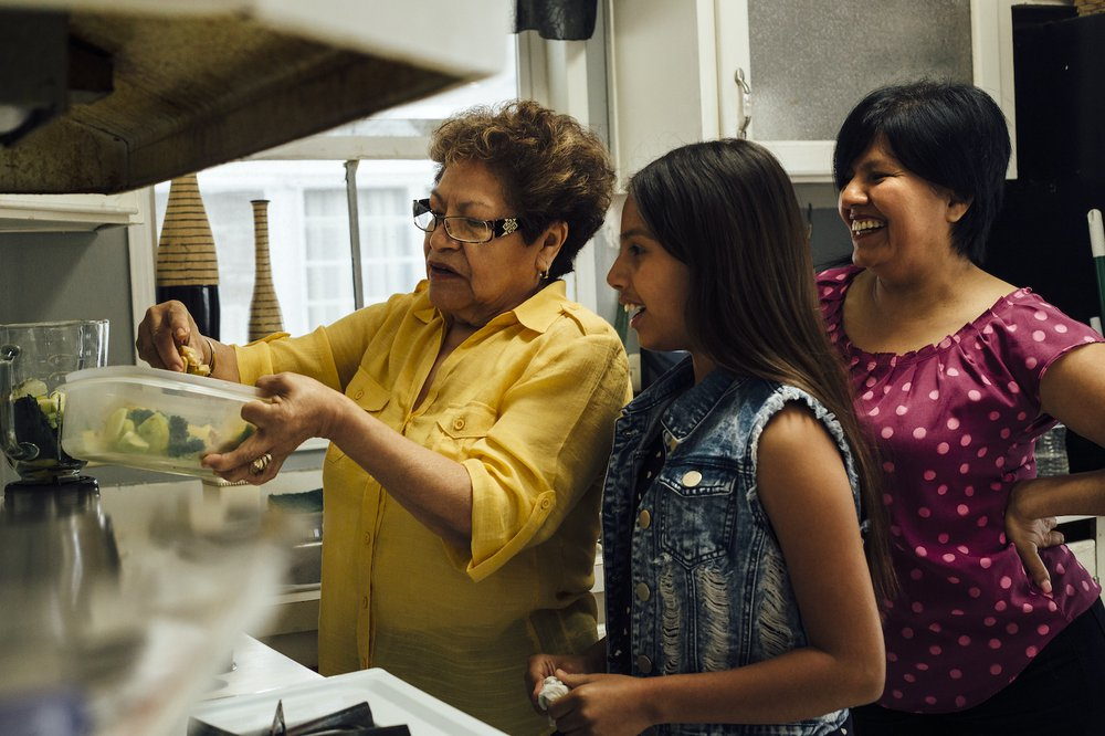 Happy women showing younger girl how to cook in the kitchen.jpg