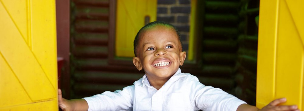 Happy young boy playing in wendy house