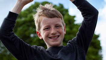 Happy young boy throwing arms in the air and smiling at the camera