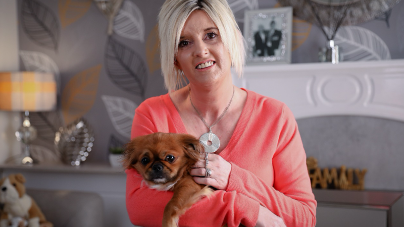 Portrait of Tanya, a foster carer, holding a small dog in her home