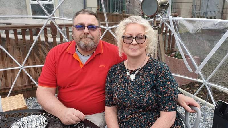 Foster carers John and Geraldine sitting close together at a table outside their home