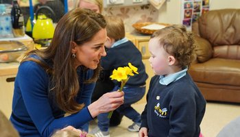 Kate Middleton kneeling down to hand flower to child at Ballymena Sure Start Childrens Centre