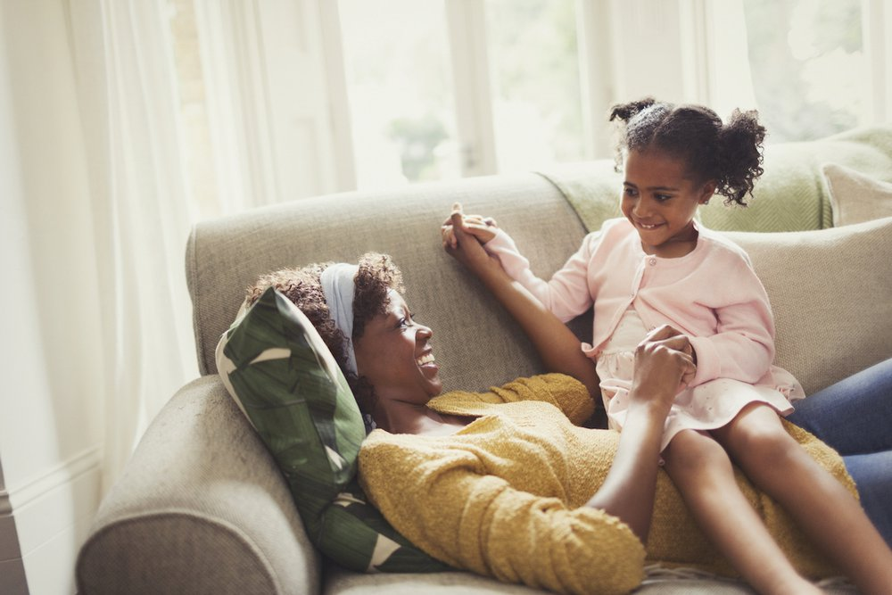 Mother and daughter laughing on sofa