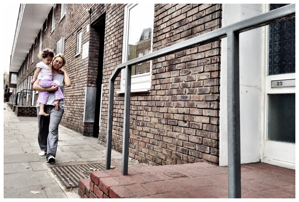 Mother and daughter walking outside council flats.jpg