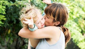 Mother kissing joyful son