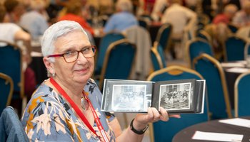 Older lady posing with old photographs at our Annual Reunion 2019