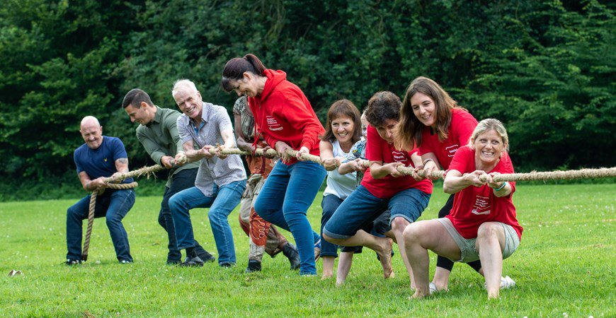 Foster families and Action for Children staff playing tug of war at an event
