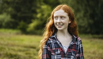 Outdoor portrait of smiling adolescent girl in woodland area