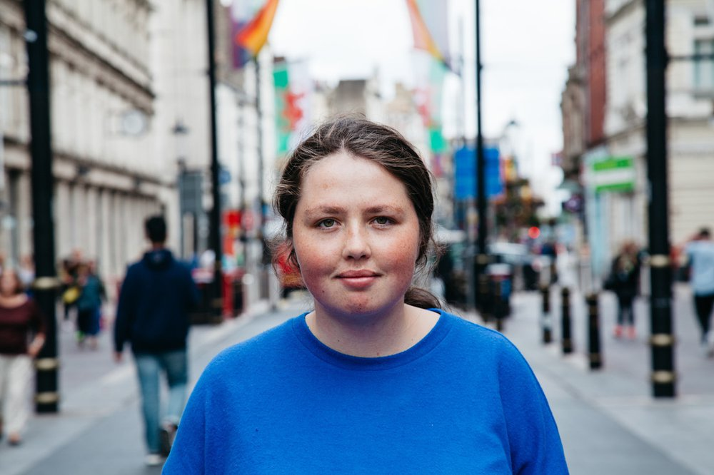 Portrait of Angharad in blue t-shirt standing in the middle of a high street