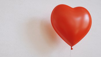 Red heart-shaped balloon against white background.jpg