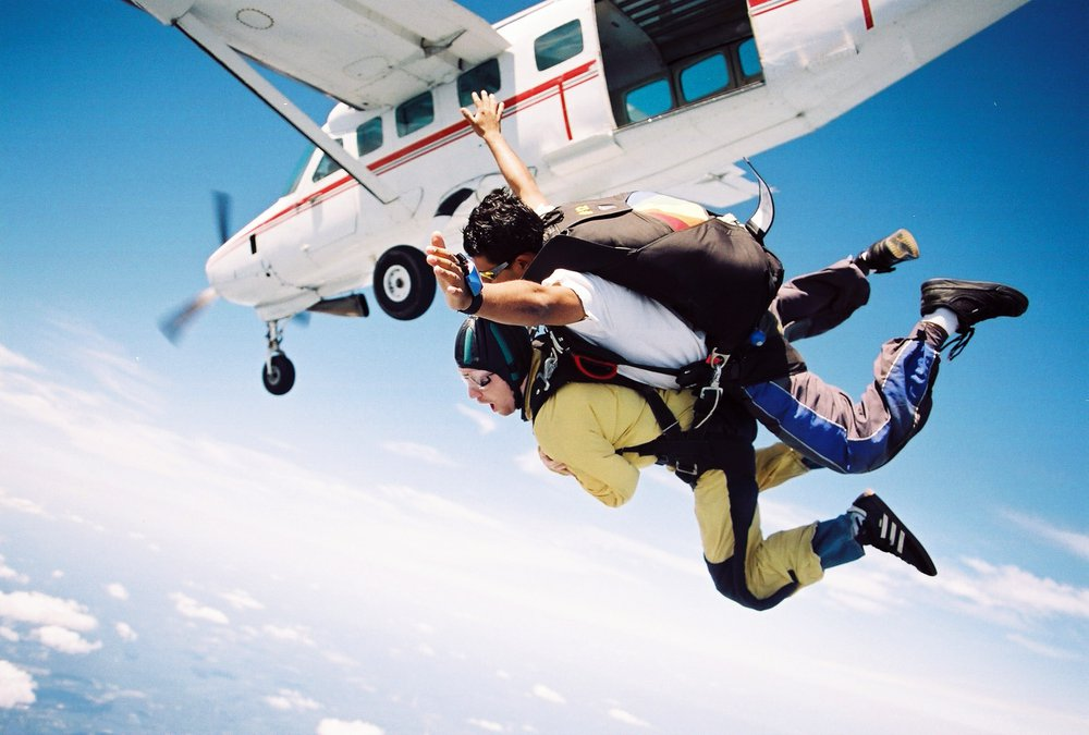 Skydivers exiting plane in the sky