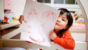 Small girl in cot holding up drawing of mermaids