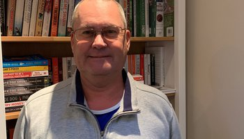 Steve Bell our Trustree standing in front of bookcase