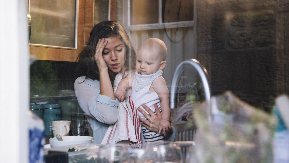 Stressed young mother in kitchen carrying baby on her hip