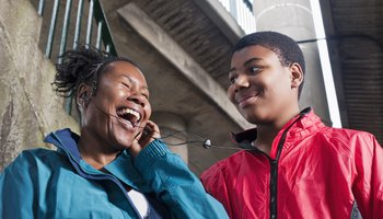 Teenage boy with mother on headphones