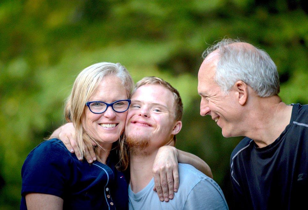 Teenage boy hugging parents.jpg
