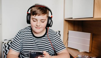 Teenage boy listening to music in his room.