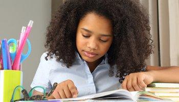 Teenage girl sitting at desk studying school books