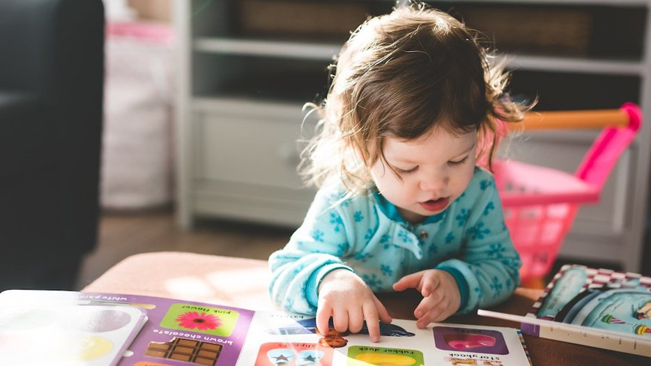 Toddler sat at coffee table reading childrens books