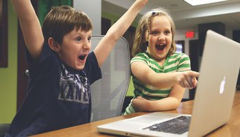 Excited and happy boy and girl looking at the laptop screen