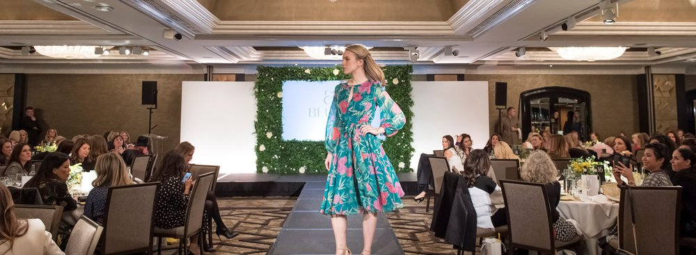 Woman in floral dress walking down the catwalk in fashion show