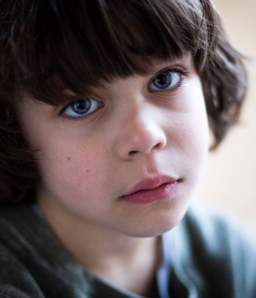 Worried young boy looking into camera