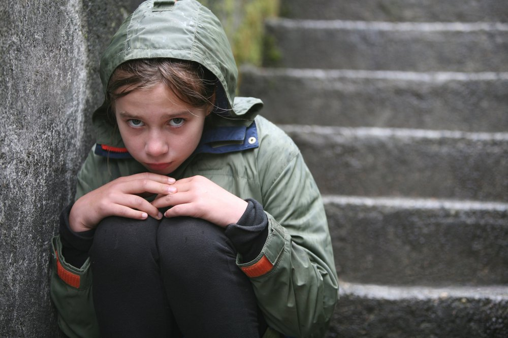 Worried young girl on stone staircase
