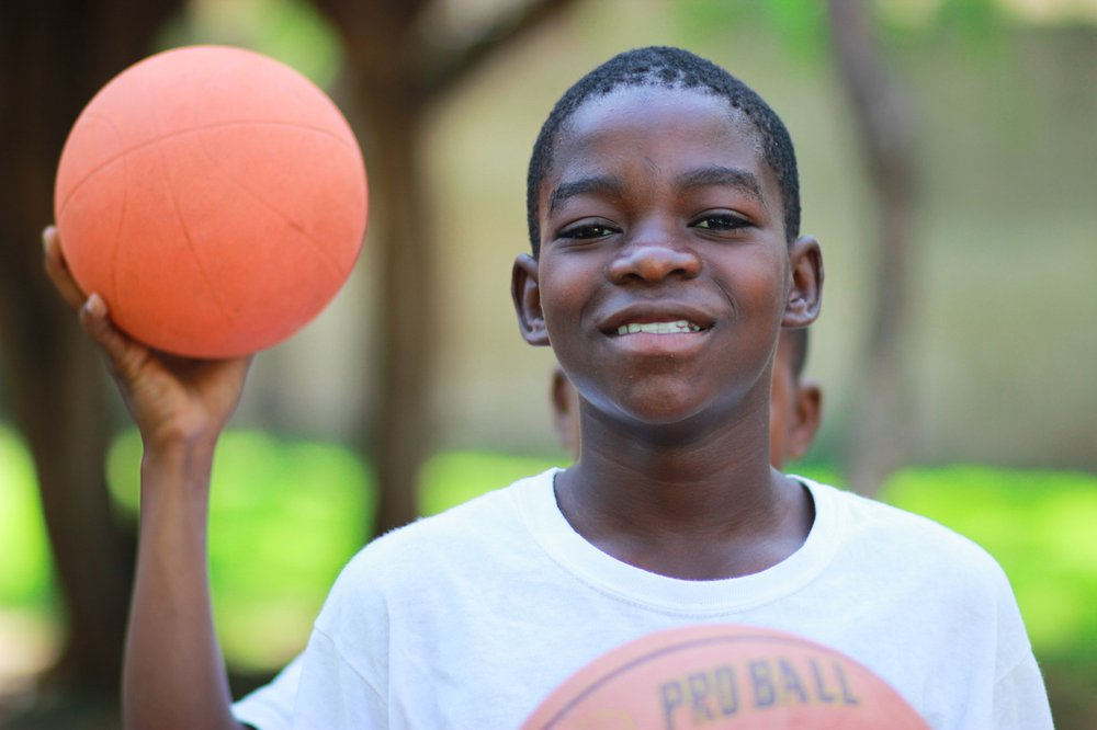 Young boy smiling and holding basketball in park
