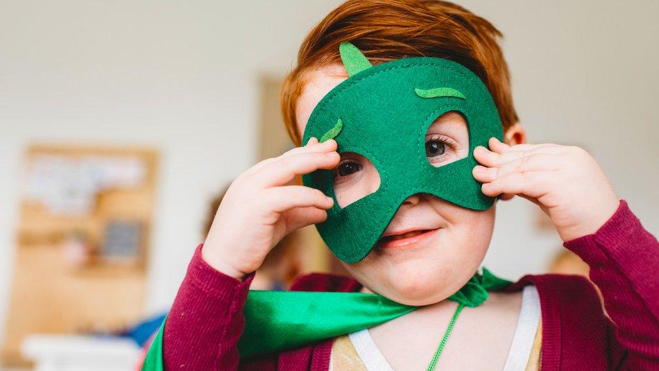 Young boy wearing superhero costume