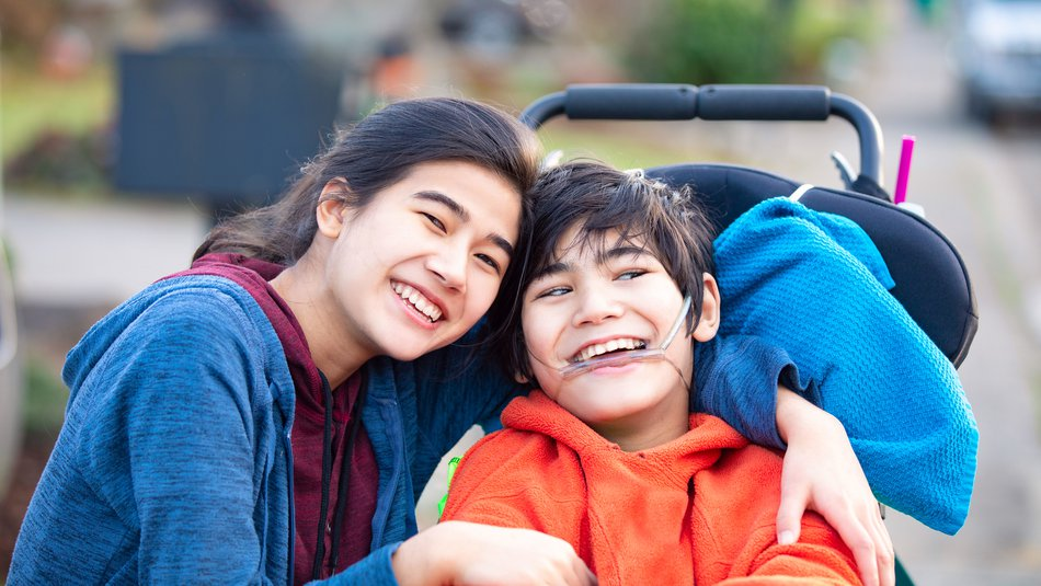 Happy young boy in a wheelchair posing with his sister