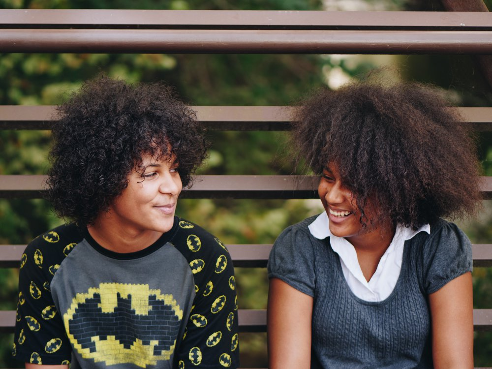 Two happy teenage girls sitting on a bench and smiling at each other