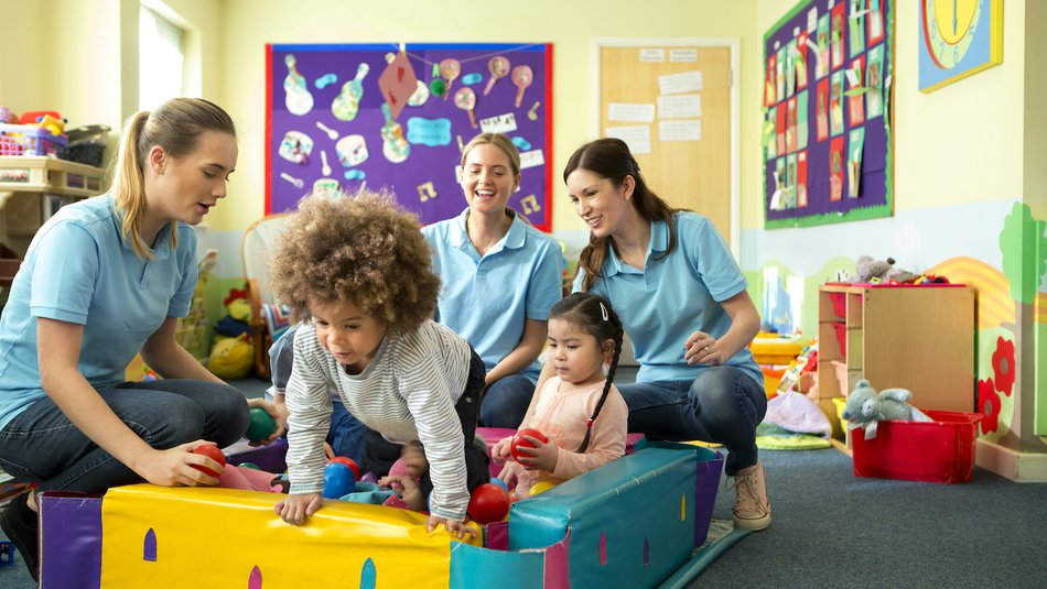 Young children playing in ball pit in nursery assisted by three workers