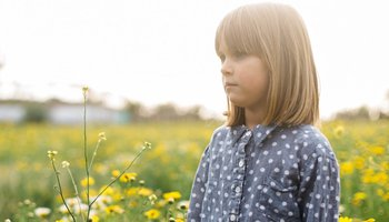 Young girl standing in field of flowers looking worries.jpg