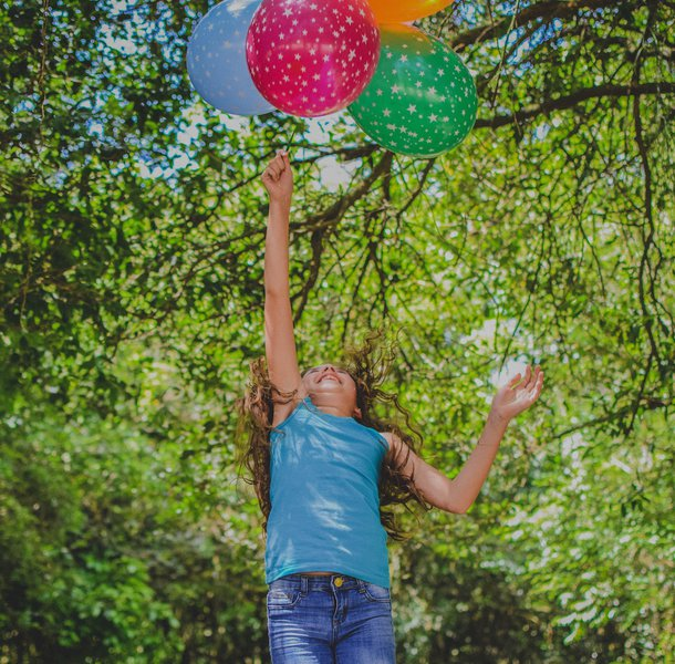 Young happy girl jumping in the air to catch balloons in park