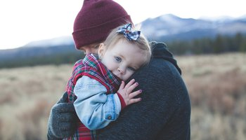 Young toddler with painted nails and father hugging outdoors