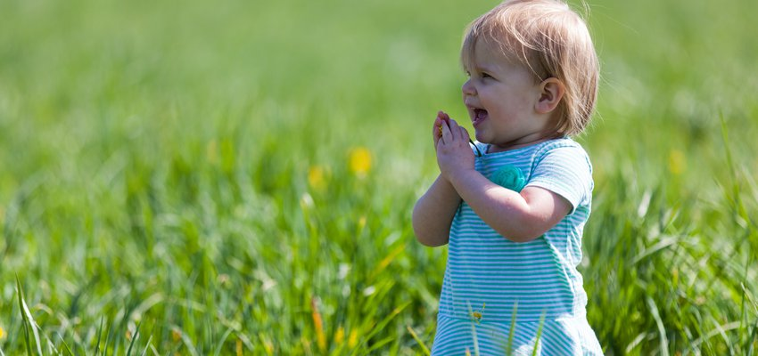 Happy toddler playing in a field of grass
