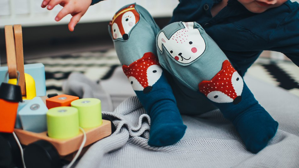 Toddler sitting on a blanket playing with wooden toys