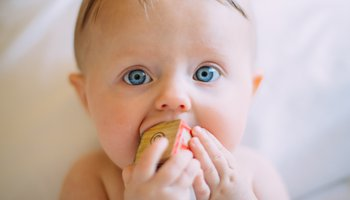 Young baby with bright blue eyes playing with a wooden block
